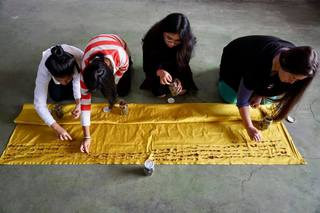 "KILL ME HONEY III  2019, CEA of the San Marcos University in Lima  Performance with the members of the CEA of the UNMSM, distributing on a large golden fabric the unknown hair bunches from the ""Kill me honey"". Ongoing participative performance"